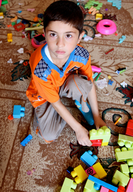 A boy with disability playing with lego toys