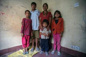 Twin sisters Jamuna, right, and Ganga Nepali, 9, pose for a portrait  with their family in the quake-damaged apartment