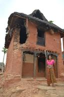 A woman stands in front of her damaged house in Sitalpati Village Development Committee in Sindhuli