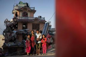 Twin sisters Jamuna, right, and Ganga, left, Nepali, 9, and their family pose for a portrait  in front of one of the buildings next to their apartment