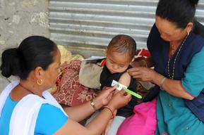 Female community health volunteer (FCHV) Krishnaa Tamang (right) uses a MUAC tape to measure the mid upper arm curcumference of three-year-old Bipasa