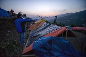 Evening falls on a camp for earthquake-displaced people atop a wind-swept ridge above the town of Charikot