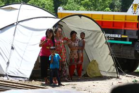 Women and children take shelter under a tent