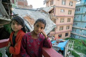 Twin sisters Jamuna, left, and Ganga, Nepali, 9, pose for a portrait  in the quake-damaged apartment