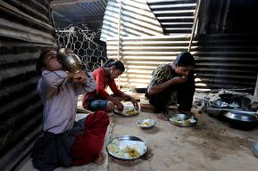 Laxmi Giri, 16, eats her morning meal with her sisters Janaki and Parbati in her temporary kitchen in Balephi village in Sindhupalchowk