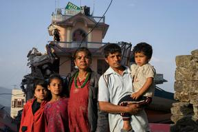 Twin sisters Jamuna, left, and Ganga Nepali, 9, and their family pose for a portrait  in front of one of the buildings next to their apartment