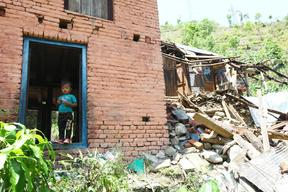 A young child stands at the doorway of his damaged house in Balefi Village Development Committee