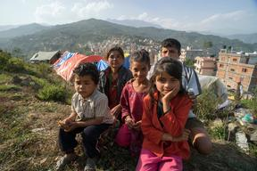 Twin sisters Jamuna, right, and Ganga, center, Nepali, 9, with their family in a tent camp for earthquake-displaced people above Charikot