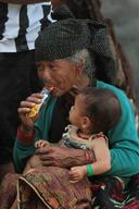 An old woman tastes juice in a packet before feeding the baby in her lap