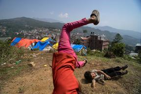Jamuna Nepali, 9, and her 4-year-old brother Anju play in the camp for earthquake-displaced people