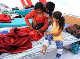 Ram Giri fastens the back brace of hIs mother Sita Giri while his sister Ramita Giri watches carefully at the Spinal Injury Rehabilitation Center in Kavrepalanchowk