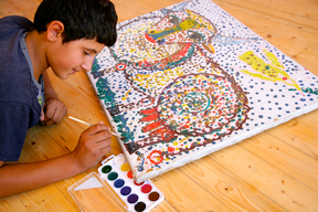 "A boy paints at the ""Umid Yeri"" Center for the Street Children."